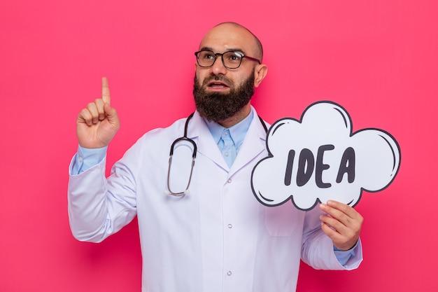 Bärtiger mannarzt im weißen kittel mit stethoskop um den hals, der brillen trägt, die sprachblasenzeichen mit wortidee halten, die beiseite mit lächeln auf intelligentem gesicht zeigt zeigefinger zeigt