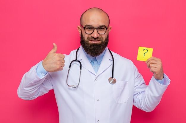 Bärtiger mannarzt im weißen kittel mit stethoskop um den hals, der eine brille trägt, die erinnerungspapier mit fragezeichen hält, das fröhlich zeigt daumen zeigt