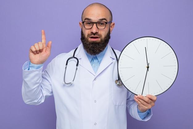 Bärtiger mannarzt im weißen kittel mit stethoskop um hals, der brille hält uhr mit lächeln auf intelligentem gesicht zeigt zeigefinger mit neuer idee