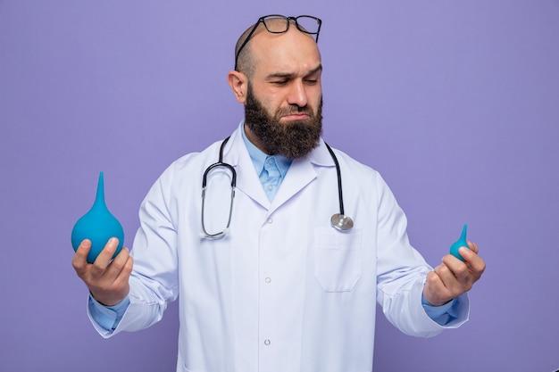 Bärtiger mannarzt im weißen kittel mit stethoskop um hals, der medizinische birnen hält, die verwirrt versuchen, wahl zu treffen, die über lila hintergrund steht