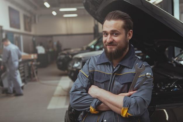 Bärtiger mechaniker, der an der autotankstelle arbeitet