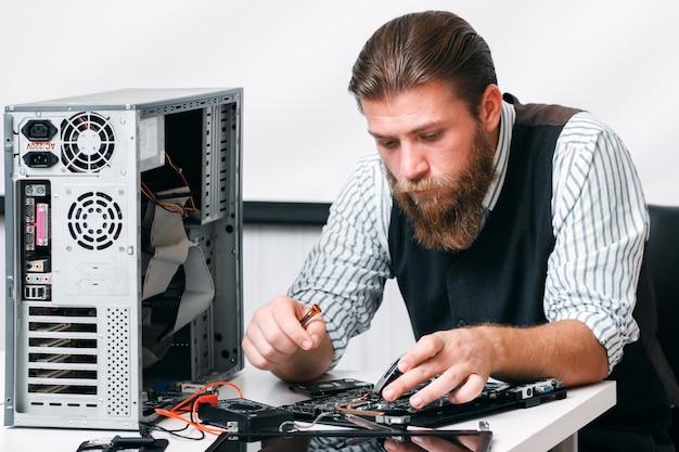 Bärtiger mechaniker repariert computerschaltung. programmiererdiagnose innerhalb eines teils der cpu. elektronische reparatur, renovierungskonzept