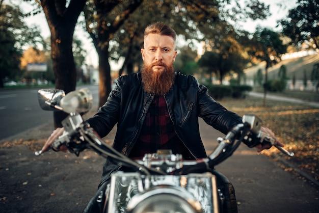 Bärtiger motorradfahrer in der lederjacke sitzt auf klassischem hubschrauber, vorderansicht. vintage fahrrad, fahrer auf motorrad