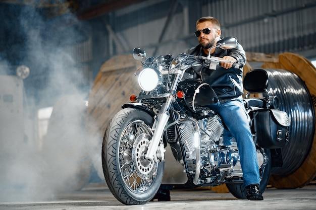 Bärtiger motorradfahrer in schwarzer lederkleidung mit seinem motorrad in der tiefgarage