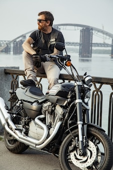 Bärtiger motorradfahrer mit seinem motorrad im sommer posiert.