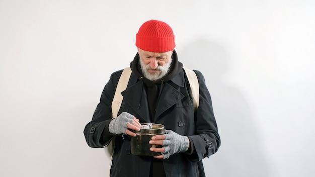 Bärtiger, obdachloser bettler alter mann, in einem mantel und in einem hut ohne geld auf einem isolierten weißen hintergrund