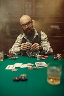 Bärtiger pokerspieler mit zigarre, casino. sucht. mann freizeit im spielhaus