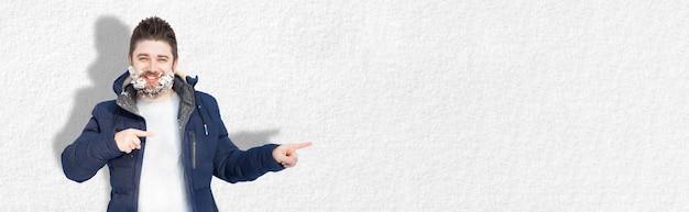Bärtiger, positiver mann im schnee, der auf banner mit platz für text zeigt, konzeptraum für ihre werbung, panoramabild, saisonale winterwerbung