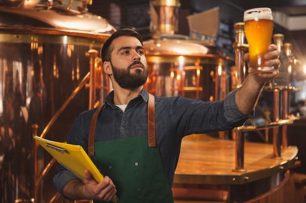 Bärtiger professioneller brauer, der klemmbrett hält und frisch gemachtes bier in einem glas untersucht