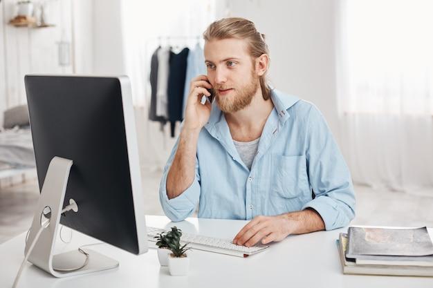 Bärtiger qualifizierter junger blonder geschäftsmann arbeitet an einem neuen projekt, sitzt vor dem bildschirm, führt telefongespräche und bespricht den finanzbericht mit dem geschäftspartner. büroangestellter plaudert mit chef