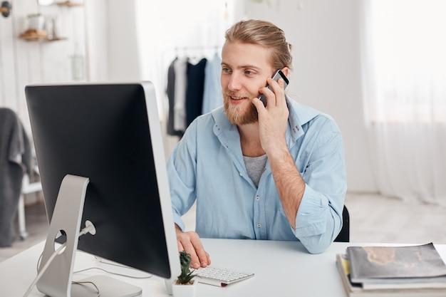 Bärtiger qualifizierter junger blonder texter arbeitet an einem neuen artikel, tippt auf der tastatur, führt telefongespräche und bespricht ein neues projekt mit einem geschäftspartner. erfolgreicher geschäftsmann hat wichtigen ruf.
