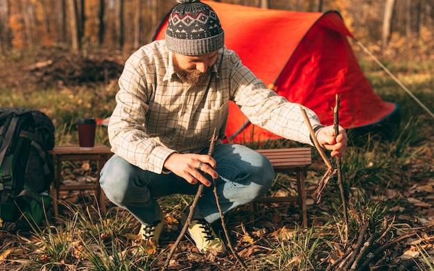 Bärtiger reisender, der feuer auf campingplatz macht