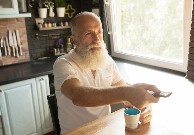 Bärtiger seniorenmann, der fernsehen mit fernbedienung sieht