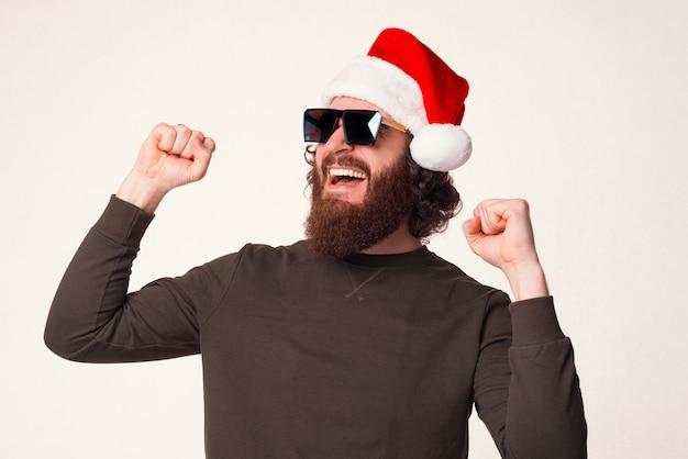 Bärtiger siegermann trägt eine weihnachtsmütze auf weißem hintergrund.