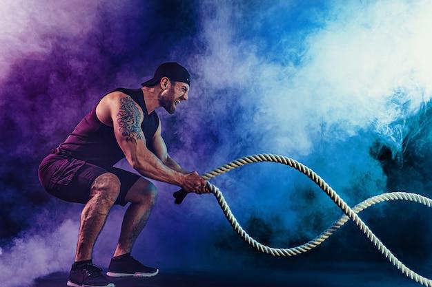 Bärtiger, sportlich aussehender bodybulder trainiert mit einem kampfseil im dunkeln mit rauch. kraft und motivation.