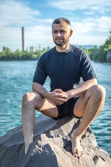 Bärtiger sportlicher mann, der auf einem felsen sitzt