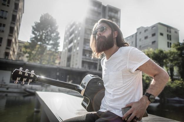 Bärtiger stilvoller mann mit einer gitarre