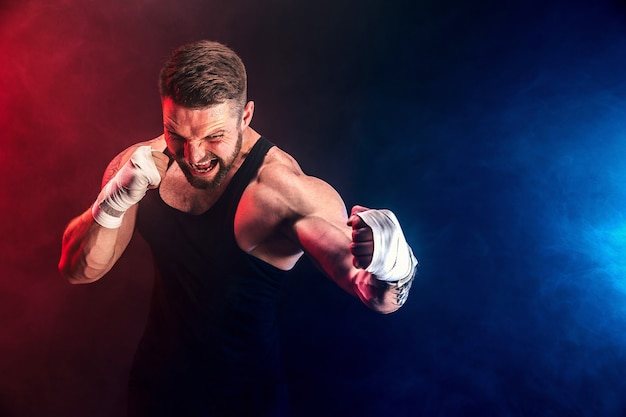 Bärtiger tätowierter portier muay thai boxer in schwarzem unterhemd und boxhandschuhen, die auf dunkler wand mit rauch kämpfen. sportkonzept.