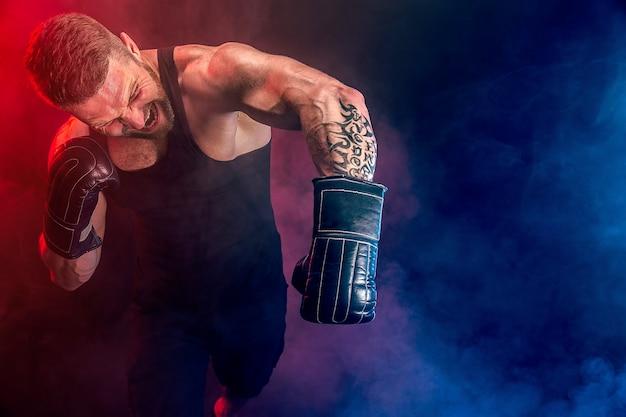 Bärtiger tätowierter sportler muay thai boxer in schwarzem unterhemd und boxhandschuhen, die auf dunkler wand mit rauch kämpfen. sportkonzept.