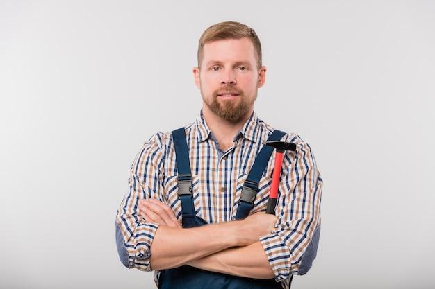 Bärtiger techniker oder handwerker in hemd und overall, der hammer hält, während arme isoliert durch die brust kreuzen