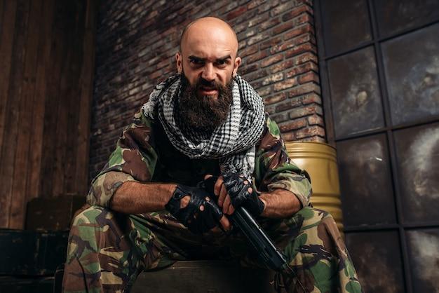 Bärtiger terrorist in uniform mit einer waffe, männlicher mojah mit waffe, wahab. terrorismus und terror, soldat in khaki-tarnung