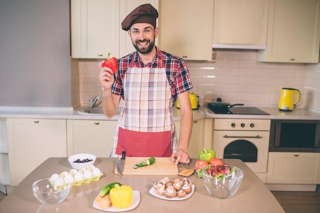 Bärtiger und hübscher kerl steht und schaut. er lächelt. junger mann hält pfeffer in der hand. er bereitet sich auf das kochen vor. er ist zufrieden