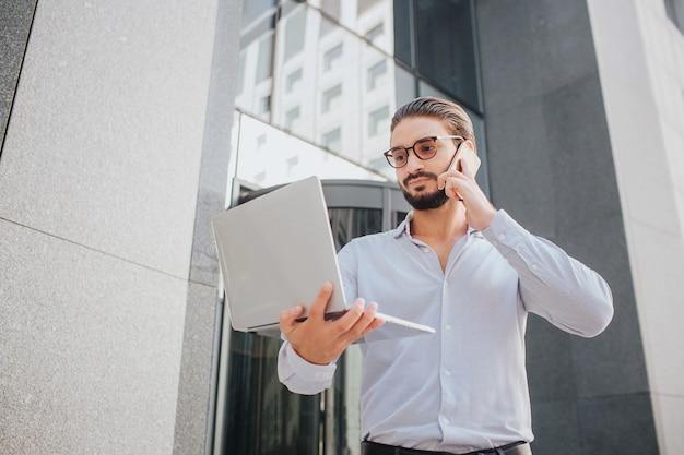 Bärtiger und junger geschäftsmann steht am gebäude und telefoniert. er hält den laptop mit einer hand und schaut auf den bildschirm. guy ist konzentriert.