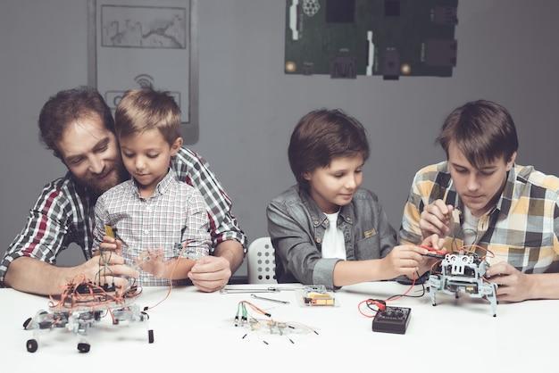 Bärtiger vater und söhne, die roboter zu hause bauen