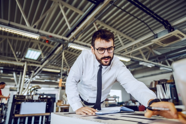 Bärtiger vorgesetzter mit brille, der die qualität der gedruckten blätter überprüft, während er in der druckerei steht.