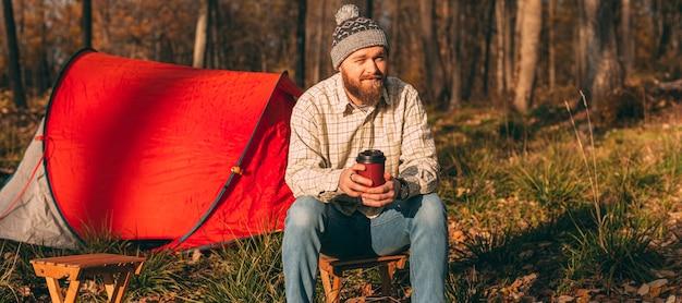 Bärtiger wanderer, der heißes getränk auf campingplatz genießt