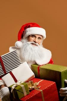 Bärtiger weihnachtsmann, der mit lots geschenken aufwirft