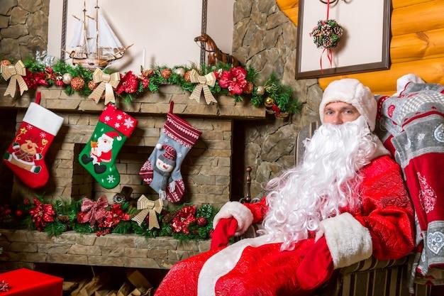 Bärtiger weihnachtsmann sitzt auf einem stuhl