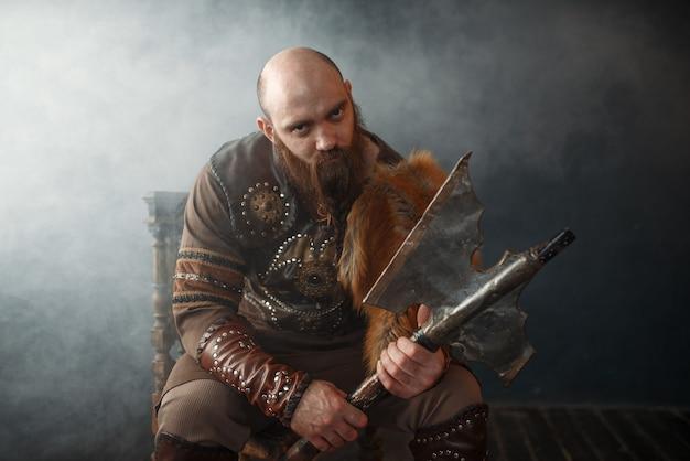 Bärtiger wikinger mit axt auf stuhl sitzend