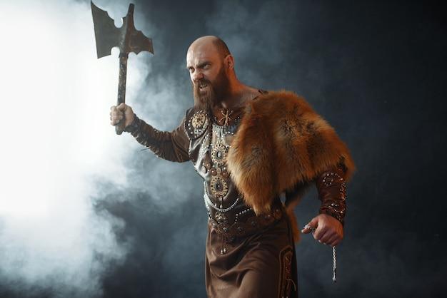Bärtiger wikinger mit axt betritt die schlacht, barbarisches bild. alter krieger im rauch