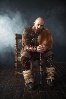 Bärtiger wikinger mit axt gekleidet in traditioneller nordischer kleidung, die auf stuhl sitzt