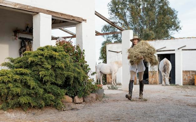 Bäuerin, die heu für ihre pferde trägt