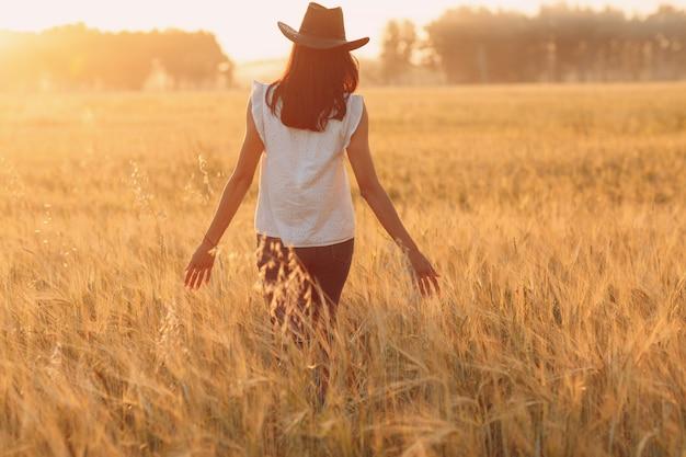 Bäuerin in cowboyhut, die bei sonnenuntergang mit den händen auf den ohren auf dem landwirtschaftlichen weizenfeld geht.
