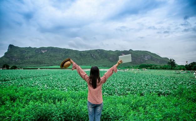Bäuerinnen die landwirtschaftlichen produkte von gemüsefarmen