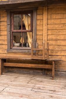 Bagel hängen im fenster eines dorfhauses. bank vor dem haus.
