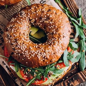 Bagel mit sahne, avocado, tomaten und arugula auf hintergrund des hölzernen brettes und der tabelle.