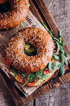 Bagel mit sahne, avocado, tomaten und rucola auf hölzernem brett.