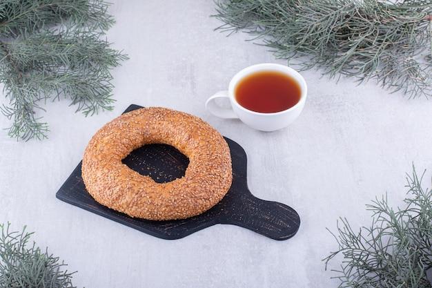 Bagel und eine tasse tee auf weißer oberfläche