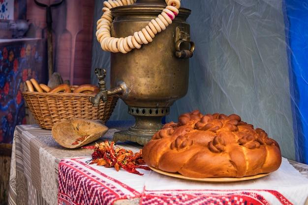 Bagels auf einem samowar, russische volksdekoration beim traditionellen fest der winterdrähte, traditionelles leben des russischen dorfes.
