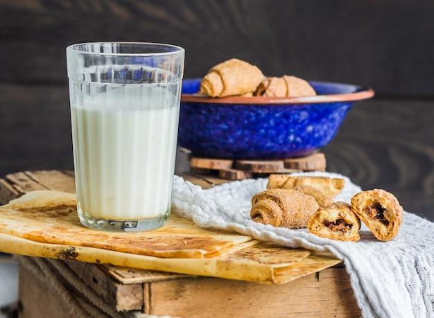 Bagels kekse aus einem kurzen gebäck mit füllung, milch, in der blauen platte süßes gebäck auf einem holz
