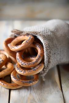 Bagels mit mohn in einem beutel auf einer holzoberfläche.