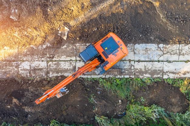 Bagger auf raupen in der fundamentgrube beim bau des gebäudefundaments, graben. luft draufsicht.
