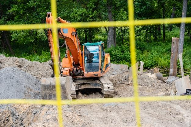 Bagger führt aushubarbeiten auf baustelle durch. gelber traktor gräbt den boden