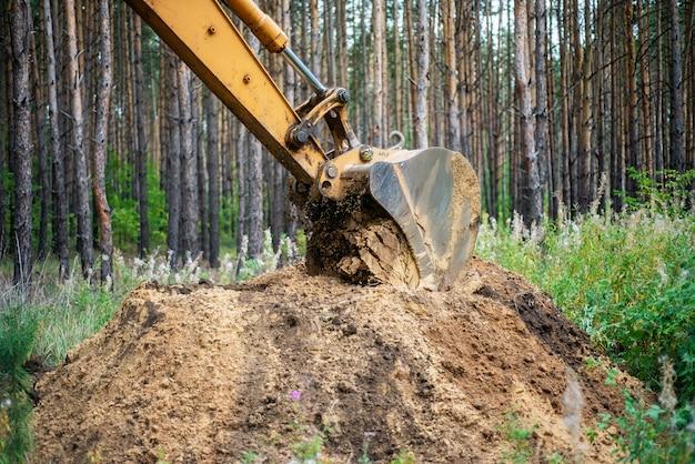 Bagger führt aushubarbeiten durch, indem er den boden mit einem eimer gräbt