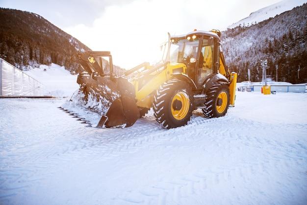 Bagger macht den weg frei nach schneefall in den bergbergen in der nähe des waldes an dem schönen sonnigen tag.