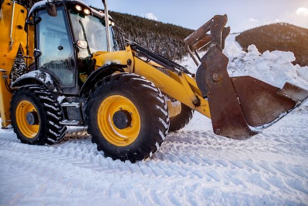 Bagger macht den weg frei nach starkem schneefall in den bergbergen in der nähe des waldes.